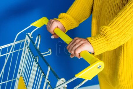 Cropped view of woman in yellow clothes holding shopping cart on blue background