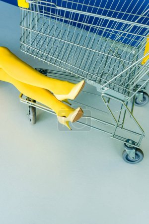 Cropped view of female legs in pantyhose by shopping cart