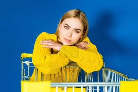 Elegant blonde woman in yellow garment leaning on shopping cart on blue background