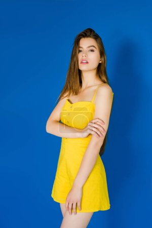 Elegant brunette woman in yellow dress posing on blue background