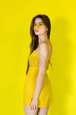 Female fashion model in yellow dress and sunglasses posing on yellow background