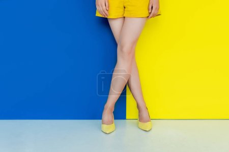 Cropped view of female legs in yellow shoes on blue and yellow background