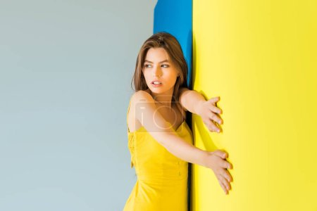 Female fashion model standing by blue and yellow background