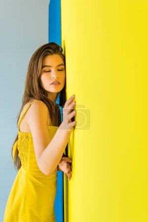 Attractive young girl leaning on blue and yellow background