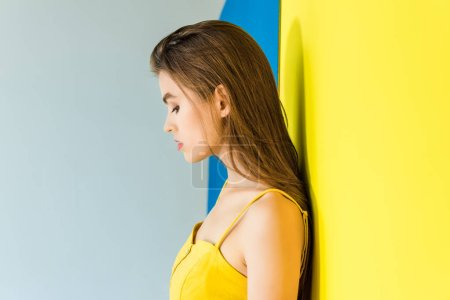 Elegant brunette woman standing by blue and yellow background