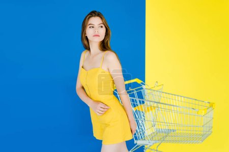 Photo for Attractive young girl standing by shopping cart isolated on blue and yellow background - Royalty Free Image