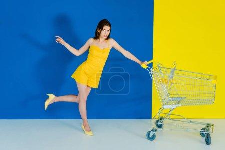 Female fashion model pushing shopping cart on blue and yellow background