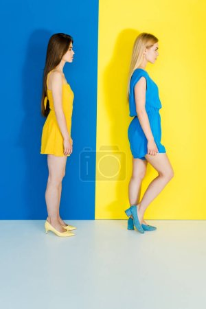 Female fashion models in contrasting clothes on blue and yellow background