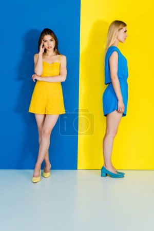 Full length portrait of women in contrasting summer clothes on blue and yellow background