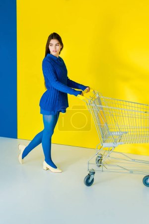 Photo for Attractive young girl with shopping cart on blue and yellow background - Royalty Free Image