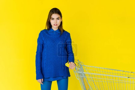 Photo for Female fashion model in blue sweater holding shopping cart isolated on yellow background - Royalty Free Image