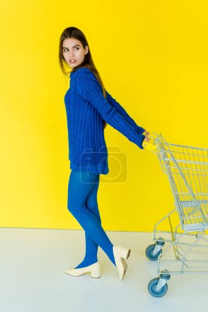 Beautiful brunette girl in blue clothes pulling shopping cart on yellow background