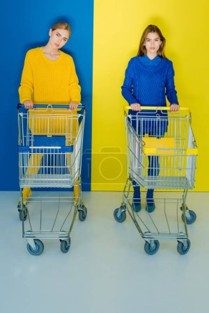Pretty girls in fashion clothes pushing shopping carts on blue and yellow background