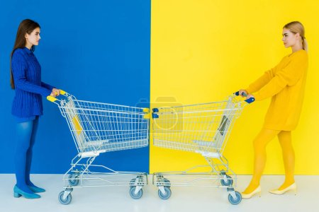 Photo for Elegant stylish women pushing shopping carts towards each other on blue and yellow background - Royalty Free Image