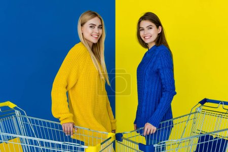 Photo for Attractive young girls holding shopping carts and smiling isolated on blue and yellow background - Royalty Free Image