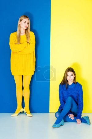 Elegant stylish women in contrasting clothes posing on blue and yellow background