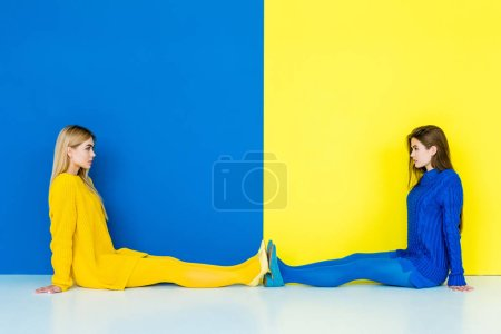 Female fashion models sitting on floor towards each other on blue and yellow background