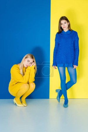 Fashionable girls in contrasting clothes posing on...