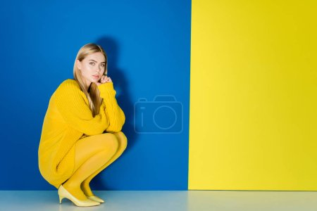 Female fashion model in yellow outfit sitting on blue and yellow background