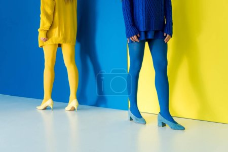 Cropped view of women in contrasting clothes standing back to back on blue and yellow background