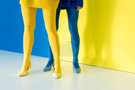 Cropped view of female legs in blue and yellow pantyhose on blue and yellow background