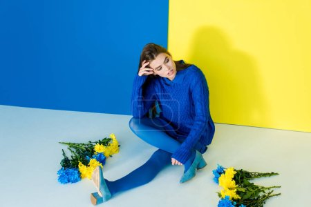Woman in blue clothes sitting among flowers on blue and yellow background