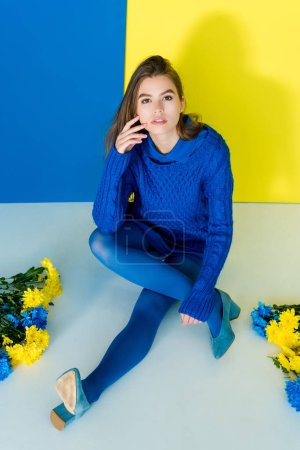 Female fashion model sitting among flowers on blue and yellow background