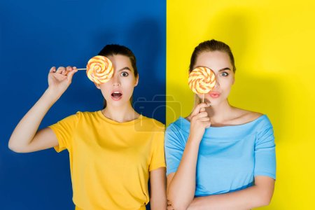 Female fashion models holding lollipops on blue and yellow background