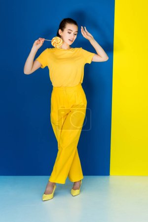 Pretty brunette girl in yellow clothes holding lollipop on blue and yellow background