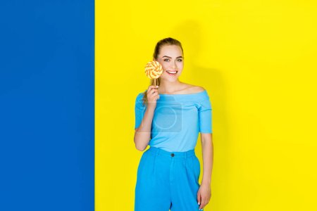 Female fashion model smiling and holding lollipop on blue and yellow background