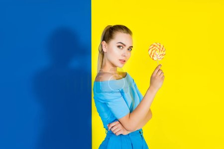 Attractive young girl holding lollipop and looking at camera on blue and yellow background