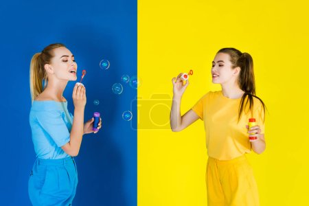 Elegant stylish women blowing bubbles on blue and yellow background