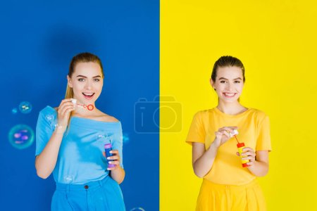 Female fashion model having fun blowing bubbles on blue and yellow background
