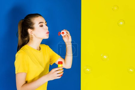 Happy young woman blowing bubbles on blue and yellow background