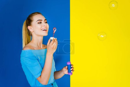 Attractive young girl blowing bubbles isolated on blue and yellow background