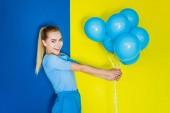 """Постер, картина, фотообои """"Привлекательные молодые Девочка держит кучу синие шары на синий и желтый фон"""""""