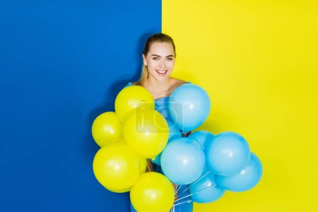 Photo for Female fashion model holding party balloons on blue and yellow background - Royalty Free Image