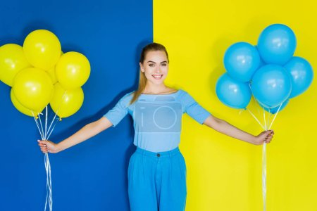 Smiling blonde woman holding blue and yellow balloons on blue and yellow background