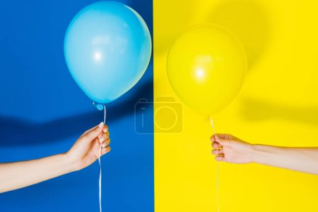 Cropped view of women hands with balloons on blue and yellow background