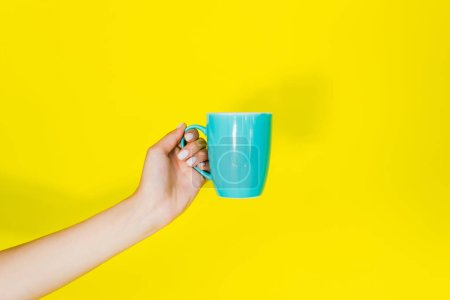 Photo for Cropped view of female hand with blue cup on yellow background - Royalty Free Image