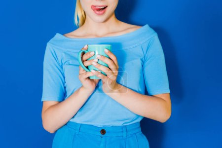 Attractive young girl in blue clothes with blue cup in hands on blue background