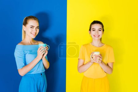 Smiling stylish women holding cups on blue and yellow background