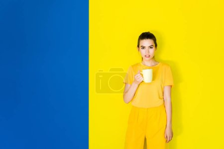 Photo for Beautiful brunette girl holding yellow cup on blue and yellow background - Royalty Free Image