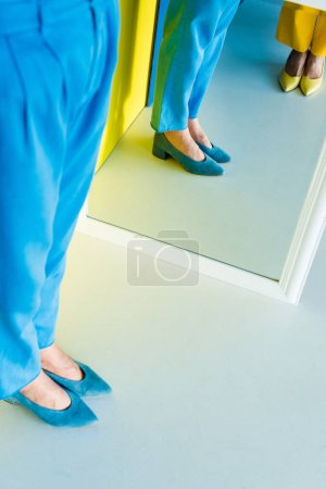 Cropped view of women posing by mirror on blue and yellow background
