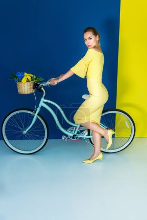 Female fashion model holding bicycle on blue and yellow background