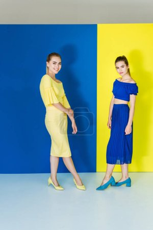 Female fashion models  in blue and yellow outfits posing on matching backgrounds