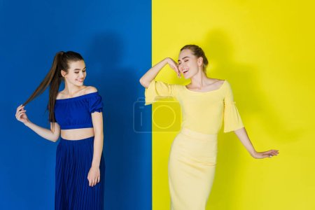 Beautiful brunette and blonde girls in blue and yellow outfits posing on matching backgrounds