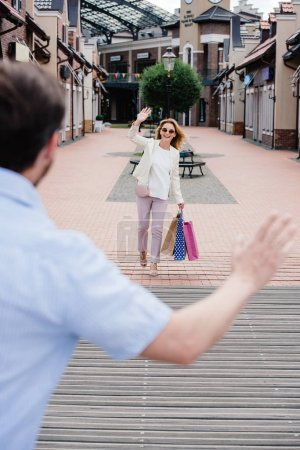 couple waving hands on street after shopping