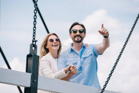 Photo pour Heureux homme pointant sur quelque chose de la femme sur le pont - image libre de droit