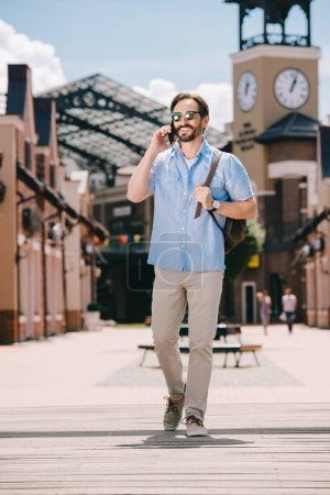 handsome man talking by smartphone and walking on street